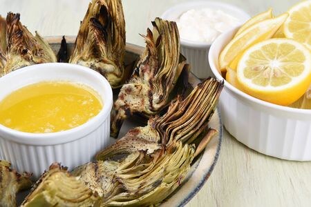 Closeup  of a palte full of grilled artichokes with butter, lemons, and mayonnaise.