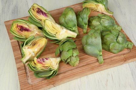 quarters: Artichoke quarters on a cutting board ready for cooking. Stock Photo