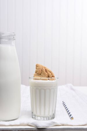 predominantly: A glass of milk with a cookie dunked inside. A bottle of milk and drinking straw in a predominantly white kitchen. Stock Photo