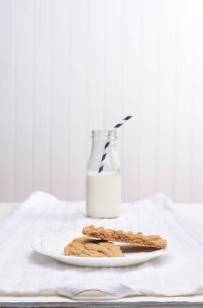 intentionally: A plate of cookies on a white plate on a white kitchen towel, A bottle of milk in the background is intentionally out of focus.