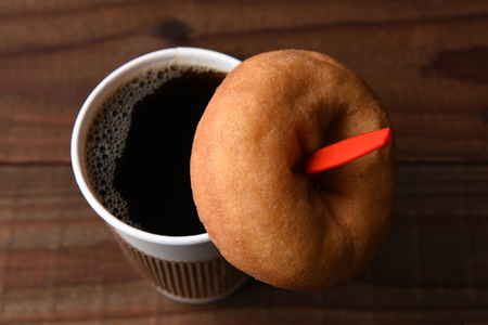 high angle view of a paper cup of hot fresh brewed coffee with a red spoon, A plain old fashioned donut is hanging on the spoon. Stock fotó