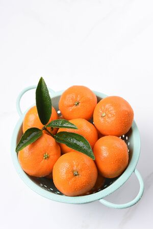 High angle view of a colander filled with fresh picked mandarin oranges.