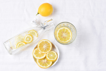 Top view of a glass of lemon water next to a swing bottle and whole piece of fruit. Horizontal format with copy space. Stock Photo