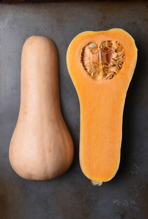 gramma: High angle view of a Butternut Squash cut in half on a metal baking sheet. Stock Photo