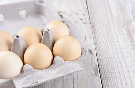 egg laying: A half dozen brown eggs in a carton on a rustic white wood table with copy space.
