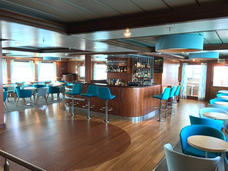 GALAPAGOS, ECUADOR - FEBRUARY 20, 2017: Santa Cruz II Cruise Ship Bar and Lounge. Guests can enjoy fantastic vistas from the comfort of the luxury ship.