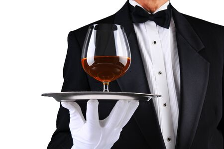 Closeup of a waiter wearing a tuxedo and holding a tray with a brandy snifter. Low angle man is unrecognizable, over white