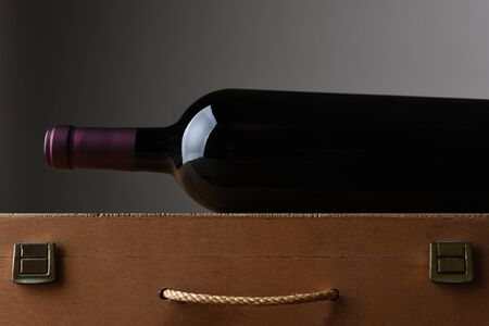 Closeup of a wine bottle laying on a wooden case. Horizontal format with copy space.