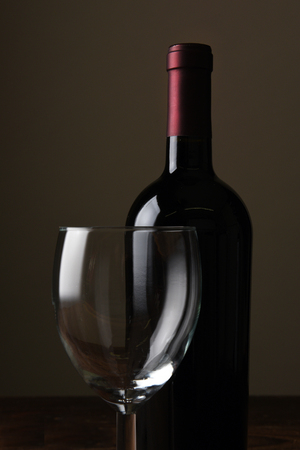Closeup of a Wine Bottle and Glass against a dark background. 写真素材