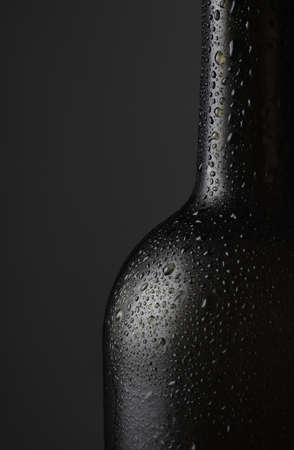Closeup of a red wine bottle covered with water droplets against a dark background with copy space. 写真素材