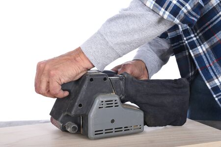 Closeup of a woodworker using a belt sander on a piece of wood. Stock Photo