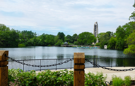 NAPERVILLE, ILLINOIS - MAY 26, 2017: Paddle Boat Quarry adjacent to the Naperville Riverwalk. The Moser Tower and Millennium Carillon rises in the distance as paddleboarders enjoy the lake. Editorial
