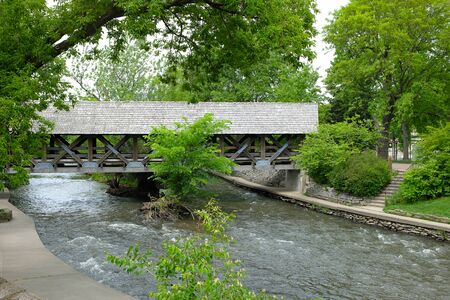 NAPERVILLE, ILLINOIS - MAY 26, 2017: Covered Footbridge across the West Branch of the DuPage River along Napervilles Riverwalk.