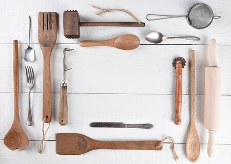 crimper: Top view of a group of cooking utensils on a rustic wood kitchen table arranged around a blank space for your copy.