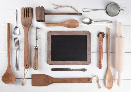crimper: Top view of a group of cooking utensils on a rustic wood kitchen table arranged around a blank chalk board. Stock Photo