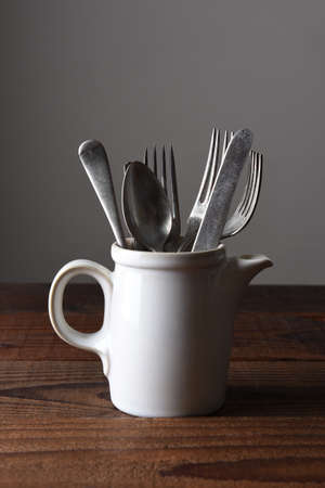 A ceramic pitcher on a rustic wood table filled with antique silverware. Vertical format with copy space.