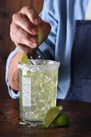 Closeup of a bartender squeezing a line into a drink glass with a salt encrusted rim. Stock Photo