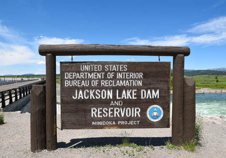 enlarged: JACKSON HOLE, WYOMING - JUNE 26, 2017: Jackson Lake Dam sign. Built in 1911 in Grand Teton National Park, it has enlarged the natural lake that is primarily fed by the Snake River. Editorial