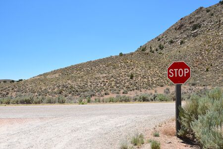 Stop sign at a gravel road intersection in the desert.