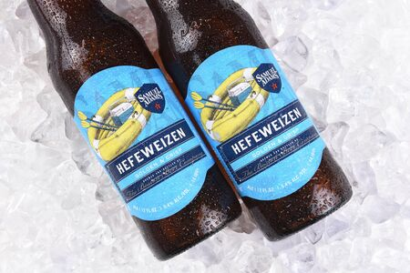 adams: IRVINE, CA - JULY 16, 2017: Samuel Adams Hefeweizen bottle on ice. From the Boston Beer Company. Based on sales in 2016, it is the second largest craft brewery in the U.S.