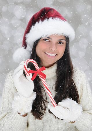 Closeup of smiling young woman holding a large candy cane. the girl is wearing a Santa hat and white sweater against a light bokeh background with snow effect. photo
