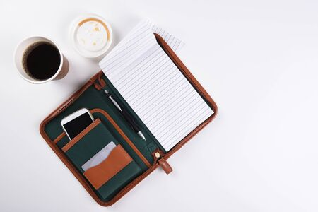 High angle shot of a white business desk, with coffee, note pad and other office equipment. Stock Photo