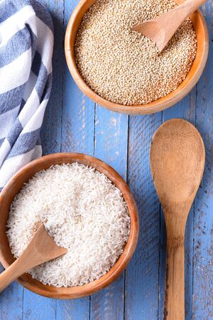 Top view of rice and quinoa in wooden bowls on a blue wood table. Stock Photo