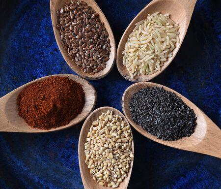 クローズ アップ 5 木製スプーンいっぱいの穀物とスパイスの平面図です。 写真素材