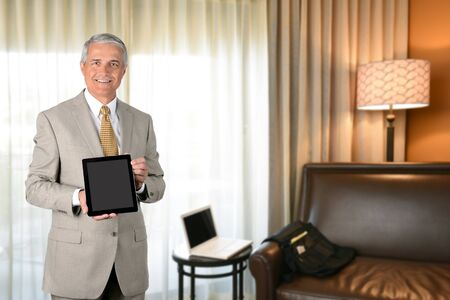 Businessman in hotel room with tablet computer. Business travel concept. photo