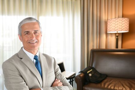 Businessman in hotel room with arms folded and looking at camera. photo