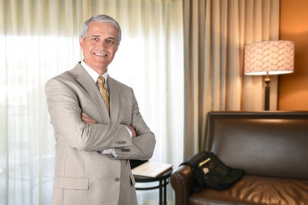 Businessman in hotel room with arms folded and looking at camera. Business travel concept. photo