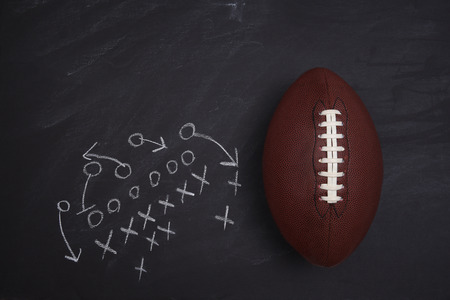 American Football and play diagram on a chalkboard. Top view with copy space. Imagens