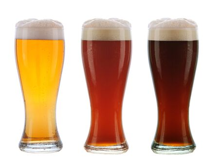 Beer: Three different beers in identical glasses with foamy tops and condensation. Stock Photo