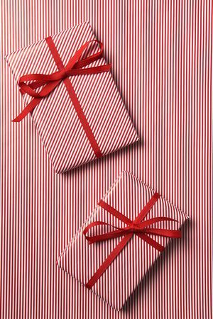Top view of two Christmas presents wrapped with red striped paper and red ribbon on a background of the same paper.