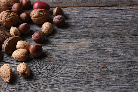 Mixed nuts on a rustic wood table with copy space, Walnuts, Pecans, Hazelnuts, Brazil Nuts and Almonds make up the array.