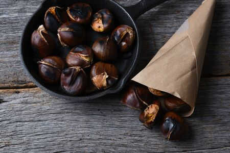 Roasted chestnuts in pan and a paper sack full of cooked nuts.