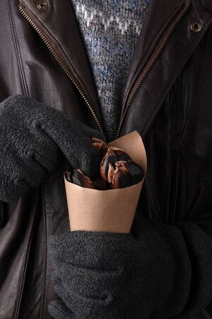 Closeup of a man in sweater and leather jacket holding a brown paper cone of fresh roasted chestnuts.