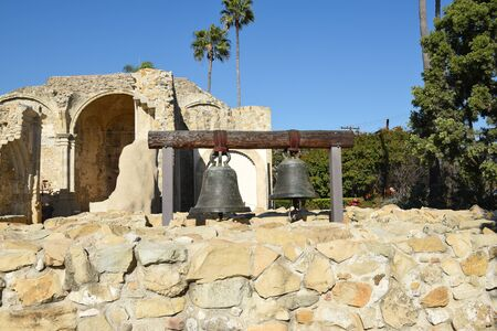 San Juan Capistrano, Ca - December 1, 2017: Original Mission Bells with the Ruins of the Great Stone Church in the background.