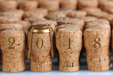 Closeup of a large group of Champagne corks, with the date 2018. Selective focus on the front row. One cork has the metal cage. Horizontal format.