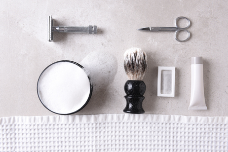 Shaving Still Life: Personal grooming accessories on a gray tile surface. Reklamní fotografie