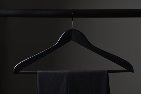 A pair of mens dark slacks hanging on a black hanger and closet rod, set against a light to dark gray background. Stock Photo