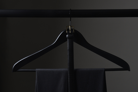 A pair of mens dark slacks and belt hanging on a black hanger and closet rod, set against a light to dark gray background.