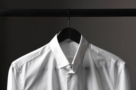 Closeup Of A White Dress Shirt On A Black Hanger And Closet Rod Against A  Light