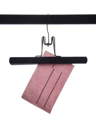 Pink receipt dangling from a black hanger against a white background. Stock Photo