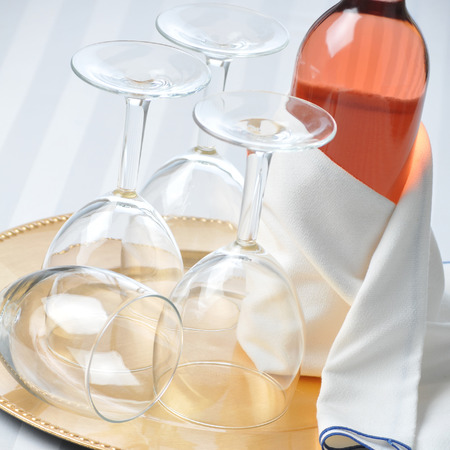 Wine Still Life: Blush Wine Bottle and Glasses on Tray with Glasses, square format. Banco de Imagens