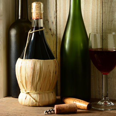 Wine Still Life: Three bottles, a wine glass and cork screw in a rustic setting, square format. Archivio Fotografico