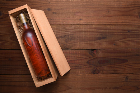 Blush Wine Box: A single Bottle of White Zinfandel wine in its wooden case on a dark wood table with copy space. Фото со стока