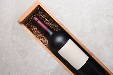 Red Wine Bottle: A single bottle of Cabernet wine in a wood case with packing straw. Bottle is at an angle with copy space on both sides. Stock Photo