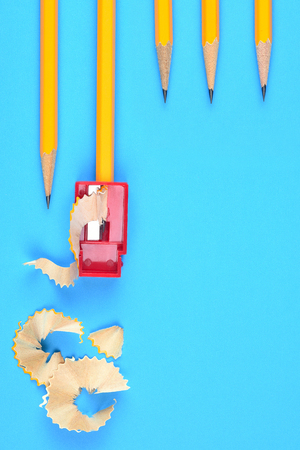 Back to School Concept: Five Yellow Pencils with a sharpener and shavings, on a blue background. Three sharpened pencils partially into frame at the top right with copy space below.