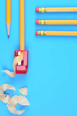 Back to School Concept: One Yellow Pencil with a point and a sharpener and shavings, on a blue background. Three pencils with eraser end enter the frame from the top right side with copy space below.